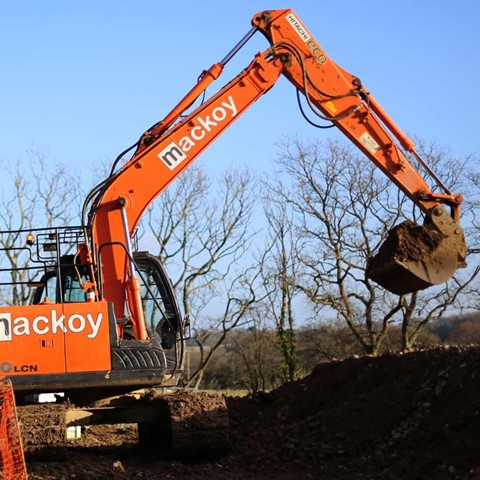 Mackoy Plant Machinery orange Excavator digging on site for new Bellway Contract in Fair Oak near Eastleigh