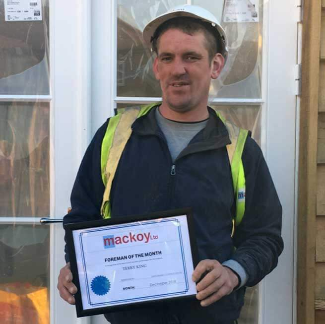 Foreman of the month December holding his award standing in front of house