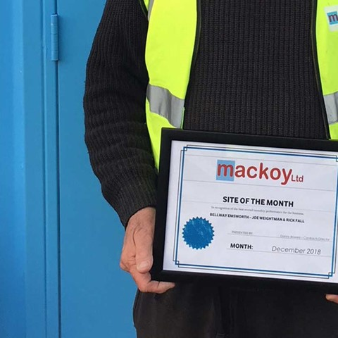 Site of the Month award held by Groundworks Foreman on front of blue container